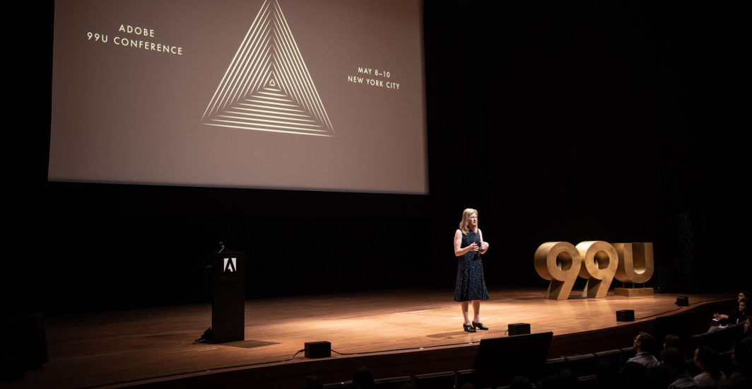 Speaker on the stage at Alice Tully Hall, with podium on the left and gold 99U sculpture on the right